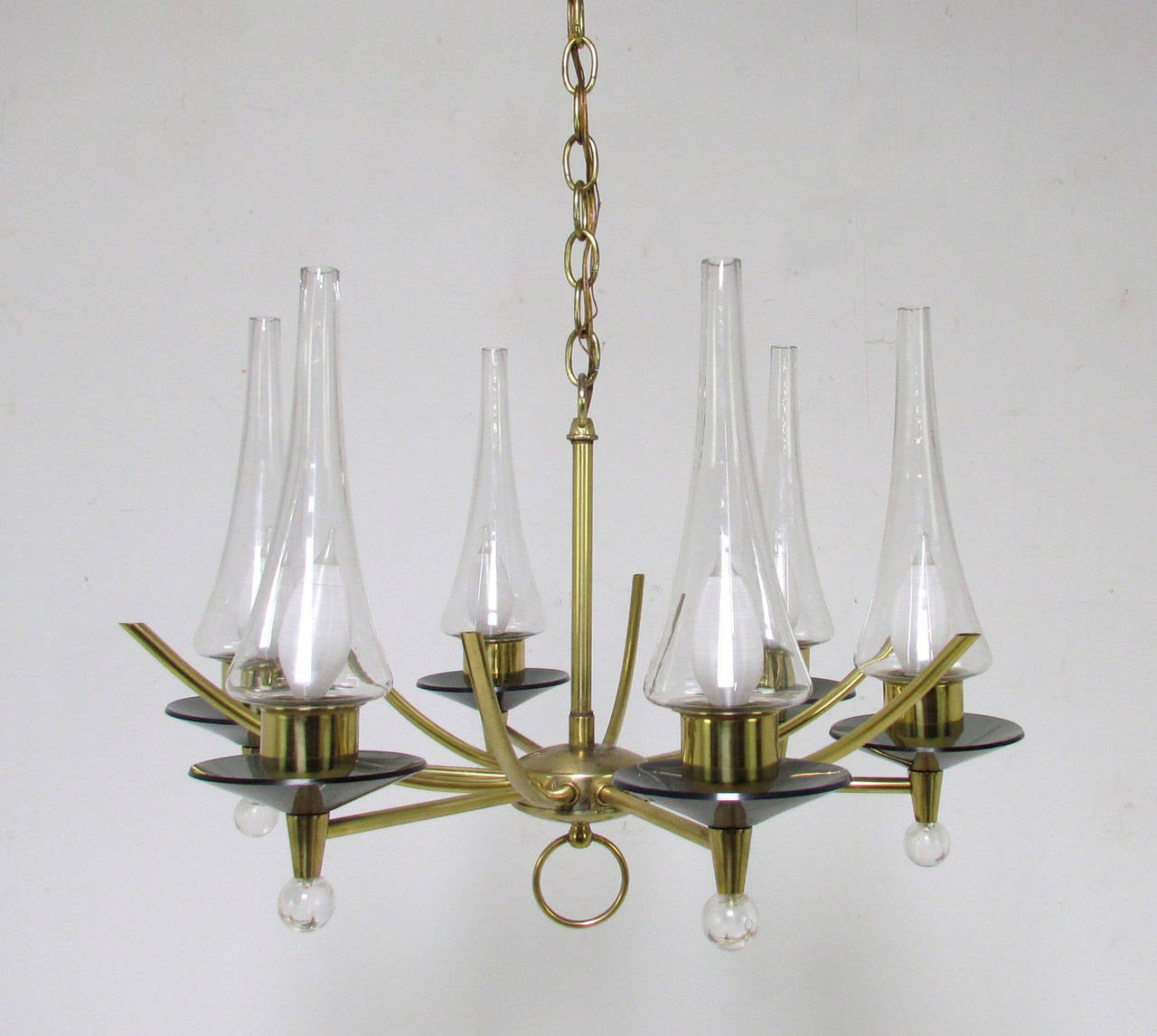 Mid-Century Modern six-arm chandelier in brass with smoked glass bobeches and elegantly tapered glass lantern shades by Feldman Co. of Los Angeles.