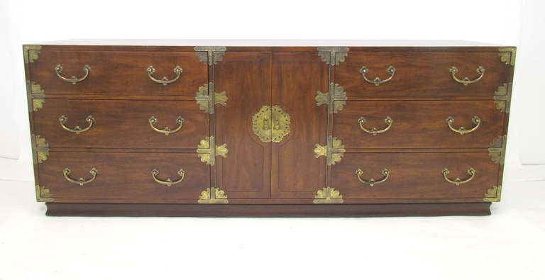 Long low campaign dresser with Asian inspired etched brass hardware by Henrendon. Rich high gloss walnut dresser features nine drawers, the middle three behind the center doors.