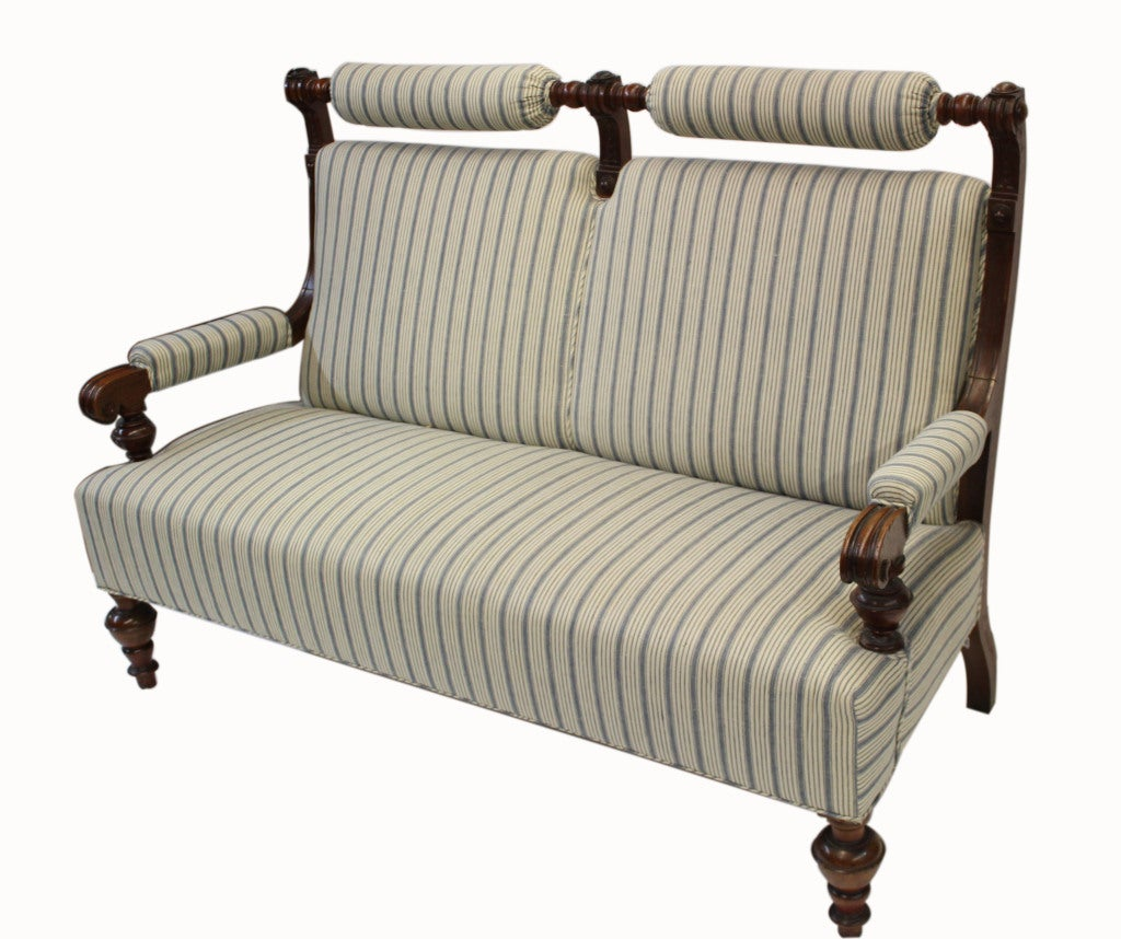 Victorian detached rolled headrest and scroll arms, all in handcrafted walnut. This piece has been recently recovered in blue striped linen fabric.