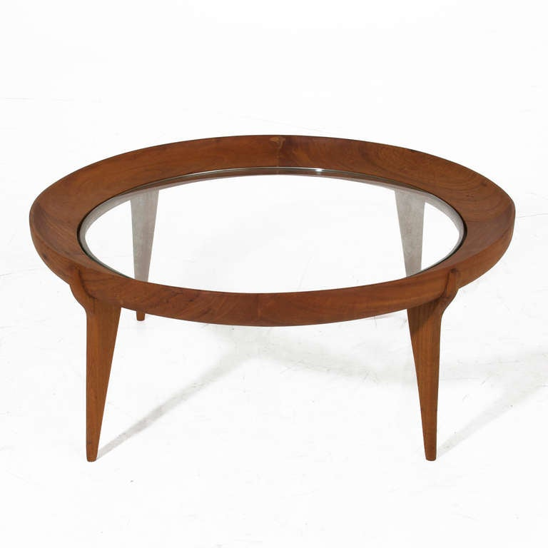 A round solid Caviuna coffee table with sculptural legs and an inset glass top designed by Brazil's Giuseppi Scapinelli. The finish is a durable water-resistent oil finish that feels like butter and protects the Brazilian hardwood.   Many pieces