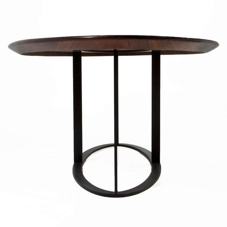Oval rosewood dining table with black steel base at 1stdibs