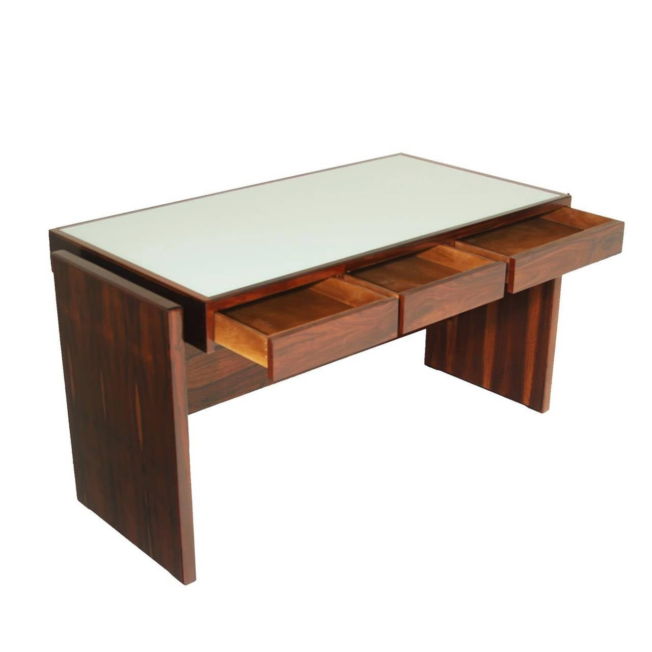 Rosewood desk designed by Brazil's Joaquim Tenreiro with a white reverse painted glass top and three drawers. This desk came from the Bloch, Editores headquarters, a building designed by Oscar Niemeyer and with interiors furnished by Sergio