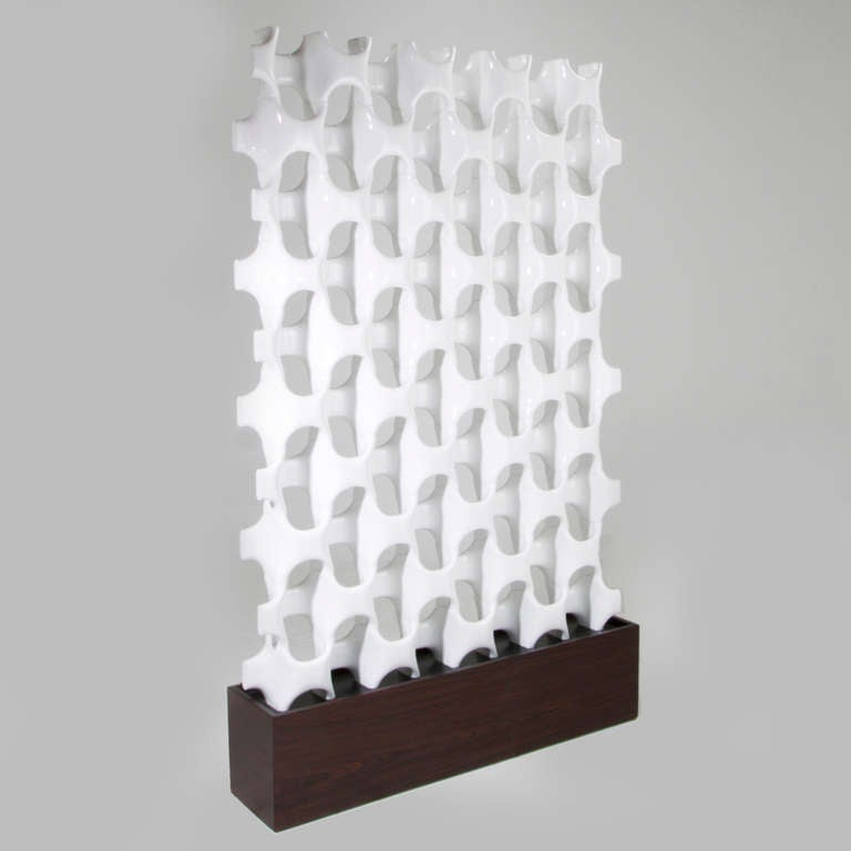 A freestanding three-dimensional sculptural room divider by Don Harvey composed of overlapping cast fiberglass ovals. The base is Rosewood with an ebonized wood plate for the divider to sit in.   Many pieces are stored in our warehouse, so please
