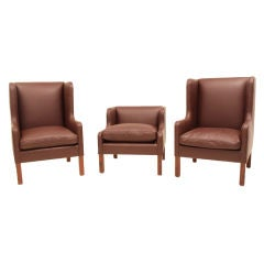 Set of three leather and rosewood arm chairs