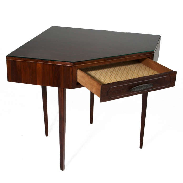 This stunning corner desk is in Solid Walnut and has the original glass top. The  legs are sculptural, and the drawer has a metal handle that is in original condition.   Many pieces are stored in our warehouse, so please click on CONTACT DEALER