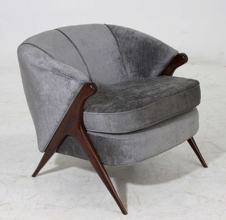 A stunning arm chair with sculptural solid wood feet and gray/blue silk velvet upholstery.