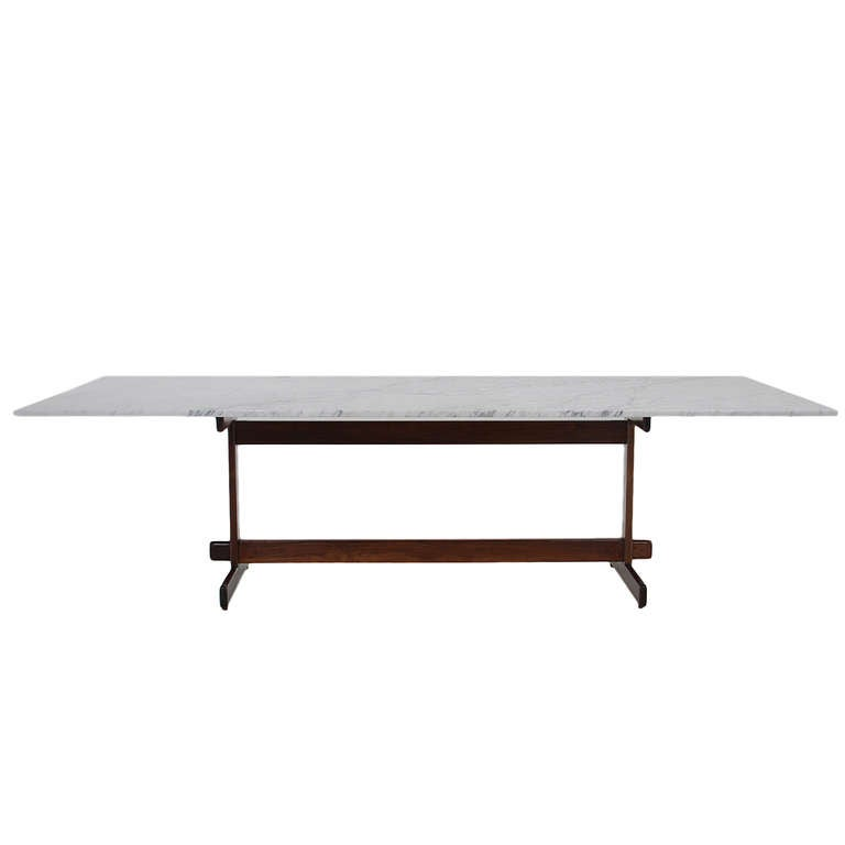 A Stunning Solid Brazilian wood base dining table with a Carrara marble top designed by Celina. The base is simply structured and very elegant.
