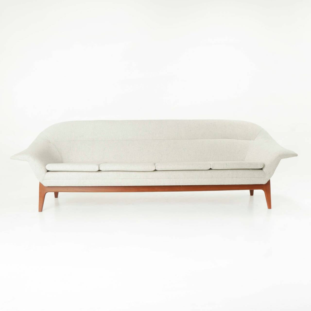 A lovely vintage sofa from Norway attributed to Rastad & Relling with sculptural solid teak base and upholstered frame with one thin seat cushion and an elegantly curved back. Fabric is speckled off-white (please refer to detail shots). 