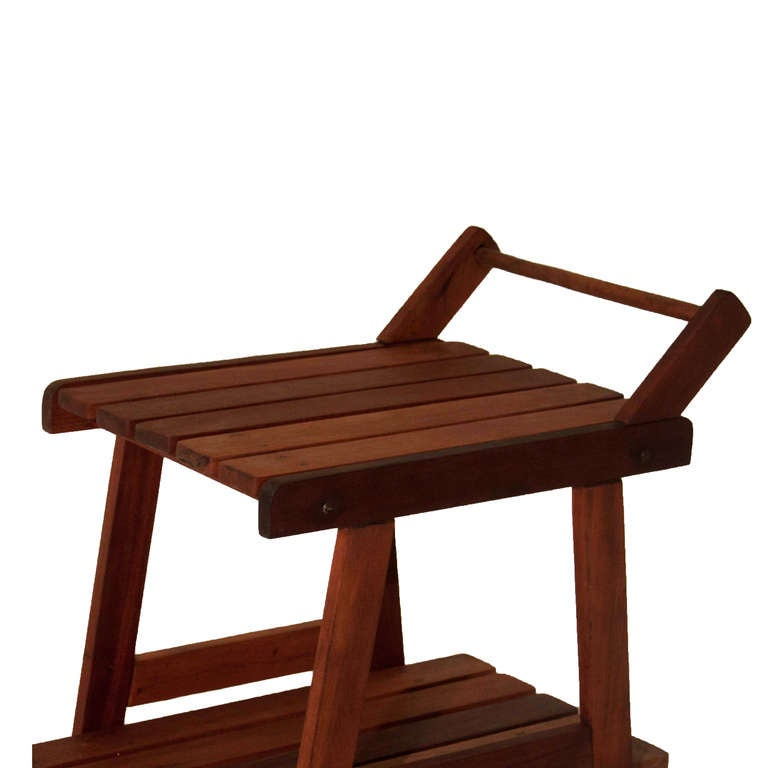 """A solid Vinhatico wood """"Taj"""" outdoor slat bar cart from Brazil by Sergio Rodrigues with two levels and a handle on blue and red rollers for easy mobility.  In order to preserve our inventory, after restoration we blanket wrap and store nearly every"""
