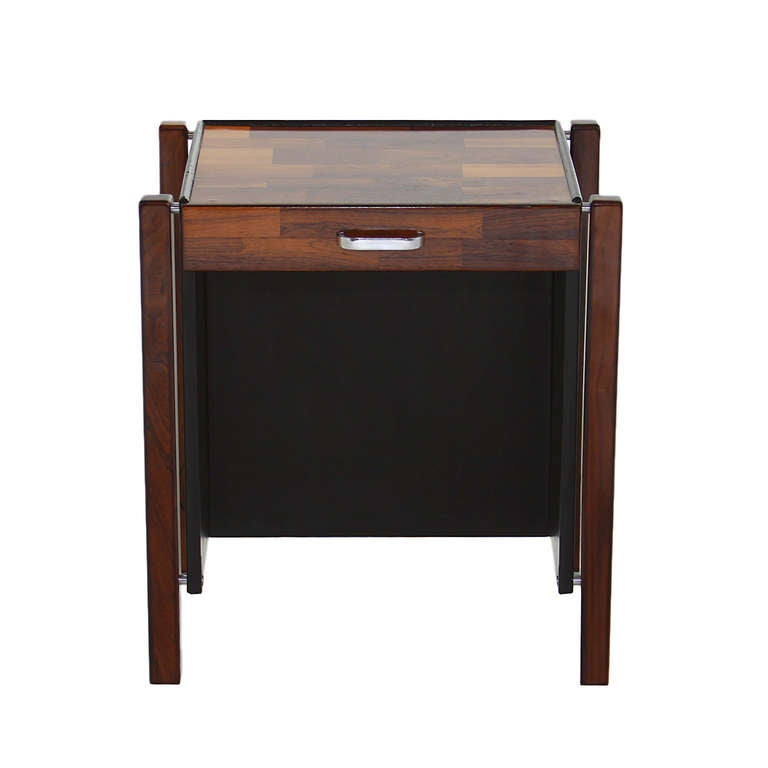 A simple patchwork Rosewood desk by Jorge Zalszupin with a single drawer and a chrome handle. The sides are black leather panels attached by chrome spacers. The top has been refinished and restored but retains stable yet apparent veneer flaws. As is