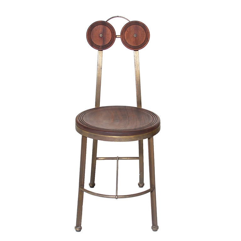 A unique single chair in a solid bronze and Freijo wood by Pedro Useche. The top has two round wood circles acting as a head rest, the circles have three carved out circles near the edge of each wood piece creating an elegant design element. The