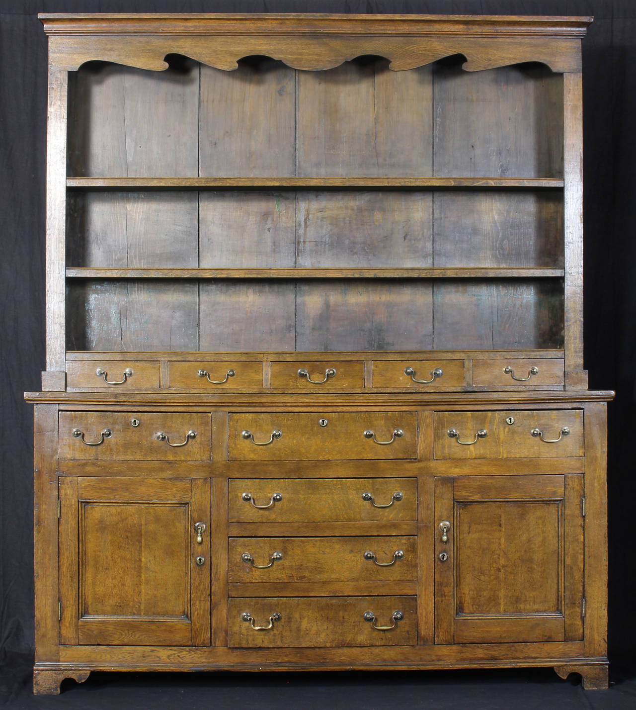 A large and impressive mid-19th century English oak dresser, with open plate rack over five spice drawers, the lower section with six drawers and two paneled doors all with original brass pulls.