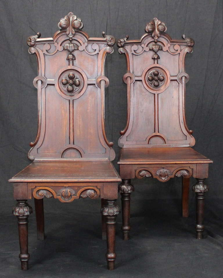 An unusually large pair of English carved mahogany Gothic Revival hall chairs dating from the 1840's.