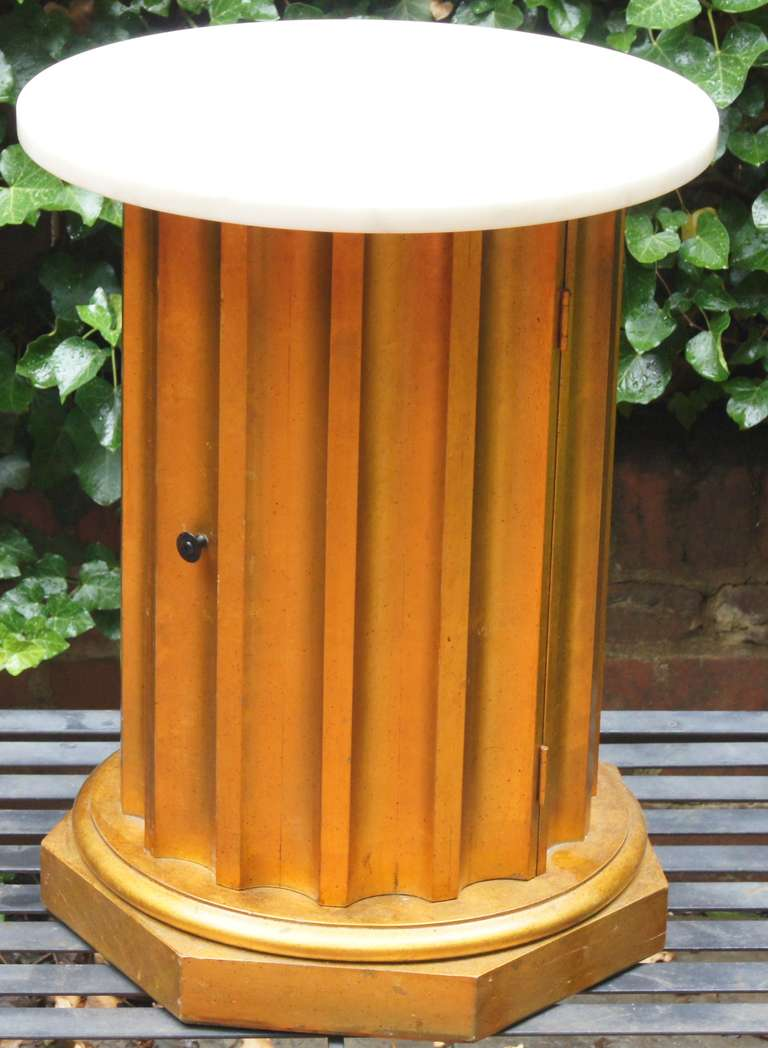 This side table is wood with a painted gold finish with light speckling (see photos).  The top is a single piece of round white marble.  It is made to resemble a Greek Doric column with a door which allows access to the interior of the column for