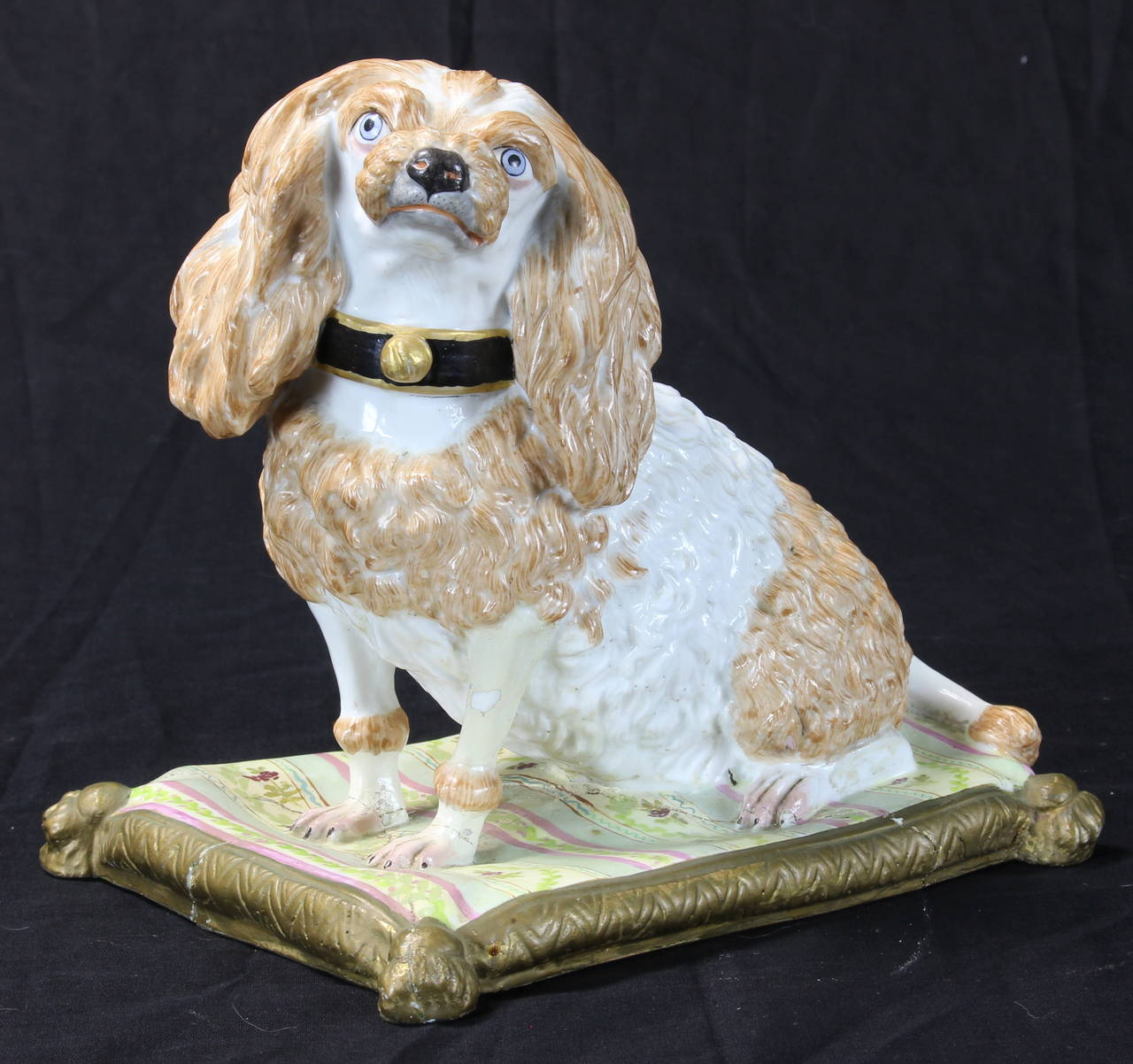 An early 19th century Meissen King Charles Spaniel resting on a colorful tasseled cushion. The base of the piece shows evidence of extensive damage and old, poorly done repairs.