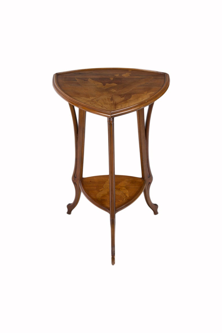 A French Art Nouveau carved wood & marquetry two-tier tri cornered table decorated with various exotic wood thistle marquetry decoration. The table is signed,