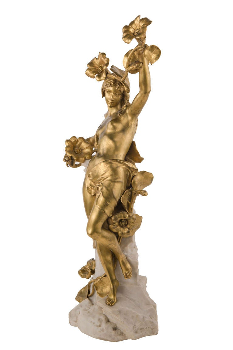 A fine and rare French Art Nouveau marble and bronze sculpture by, Jean-Baptiste Germain of a gilt bronze partially nude maiden entwined with in a floral leaf and vine resting on a white marble column. The sculpture is signed,