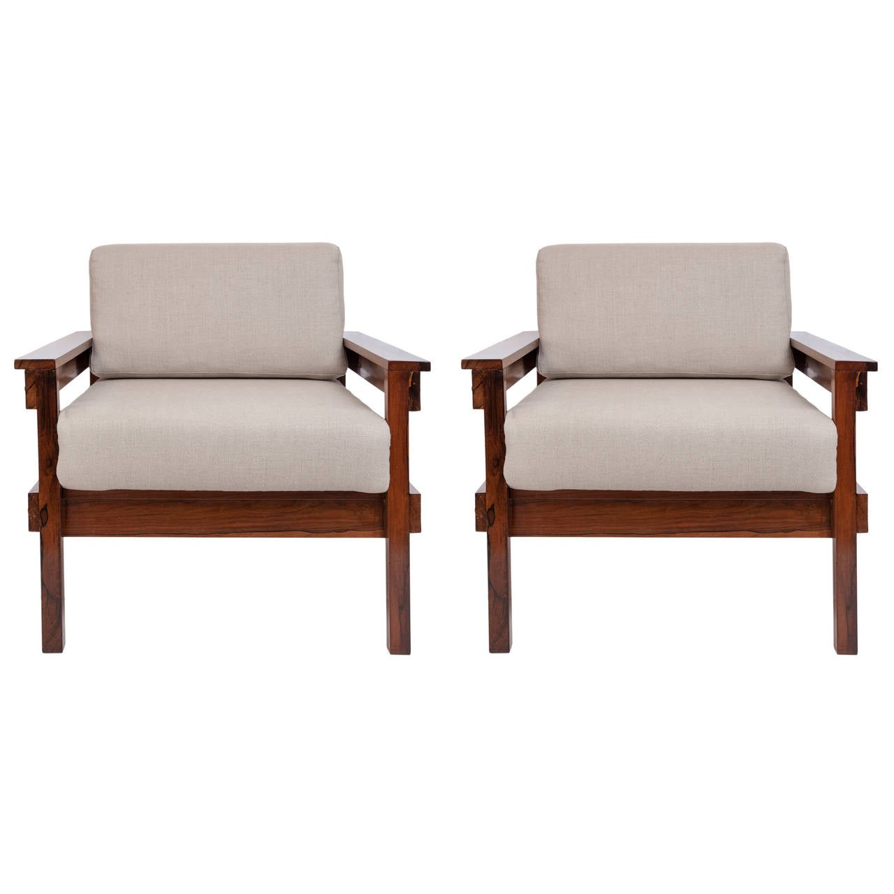 A vintage pair of lounge armchairs, produced circa 1960's, with Brazilian Jacaranda wood frames, cushioned back and seat upholstered in beige linen. Very good condition, consistent with age and use, recently reupholstered.