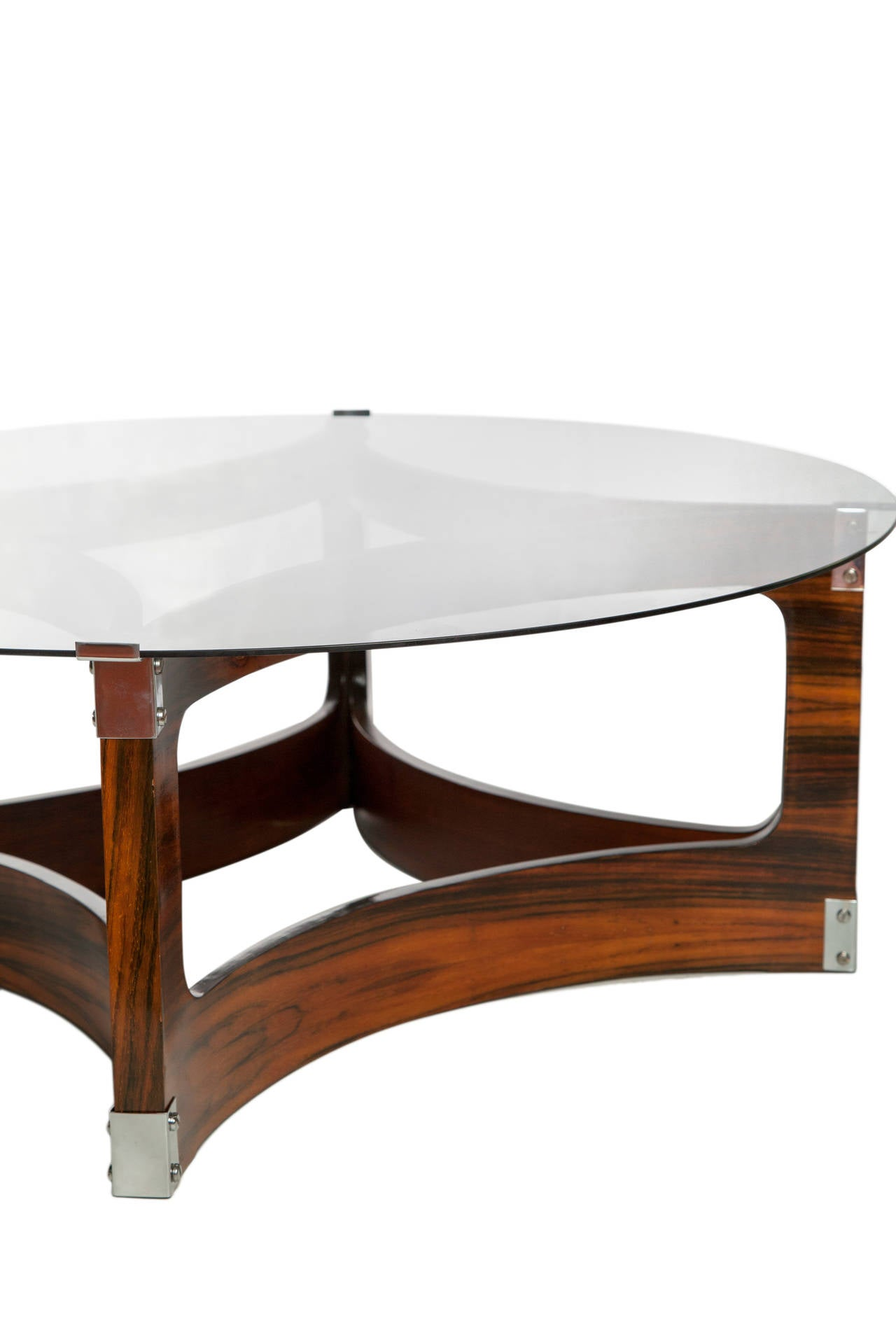 A vintage coffee table, produced, circa 1960s by designer Jorge Zalszupin for L'Atelier, with round smoked glass top, on a curved, diamond shaped frame base in Brazilian jacaranda wood, with chrome-plated supports to the corners. Good condition,
