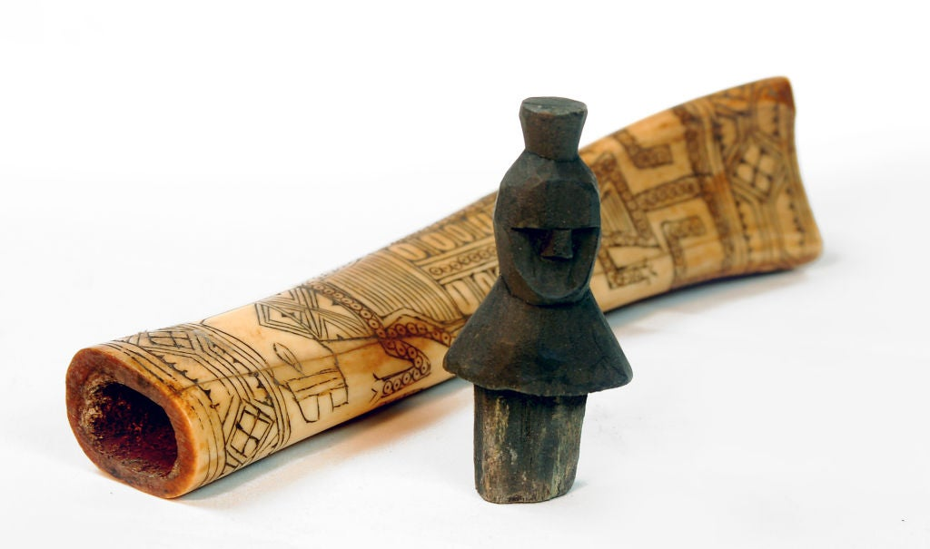 This carved cow bone with lizard motif was made by the Batak people from the highlands of North Sumatra in Indonesia. The ornately decorated bone is hollow and used to store medicinal herbs. A figurative carved wooden head is used for a stopper. The