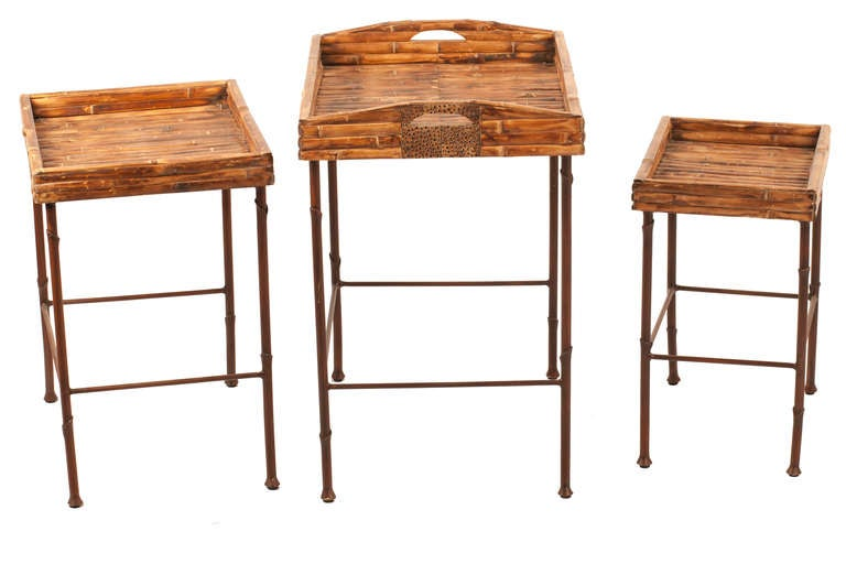 Late 20th century, Tommy Bahama style set of three nesting tables fit inside each other. Wrought iron bases, attached burnt bamboo tray tops.