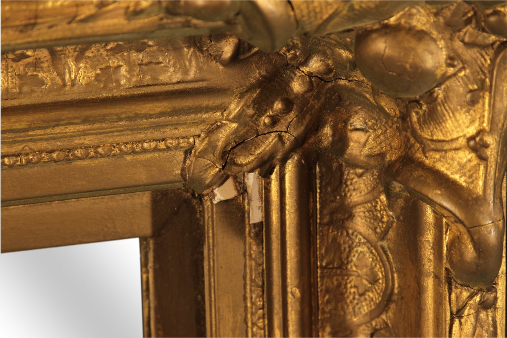 This 19th century Baroque style giltwood mirror features not only intricate carvings but a lovely gilt repousse border. With nicely articulated foliate corners.