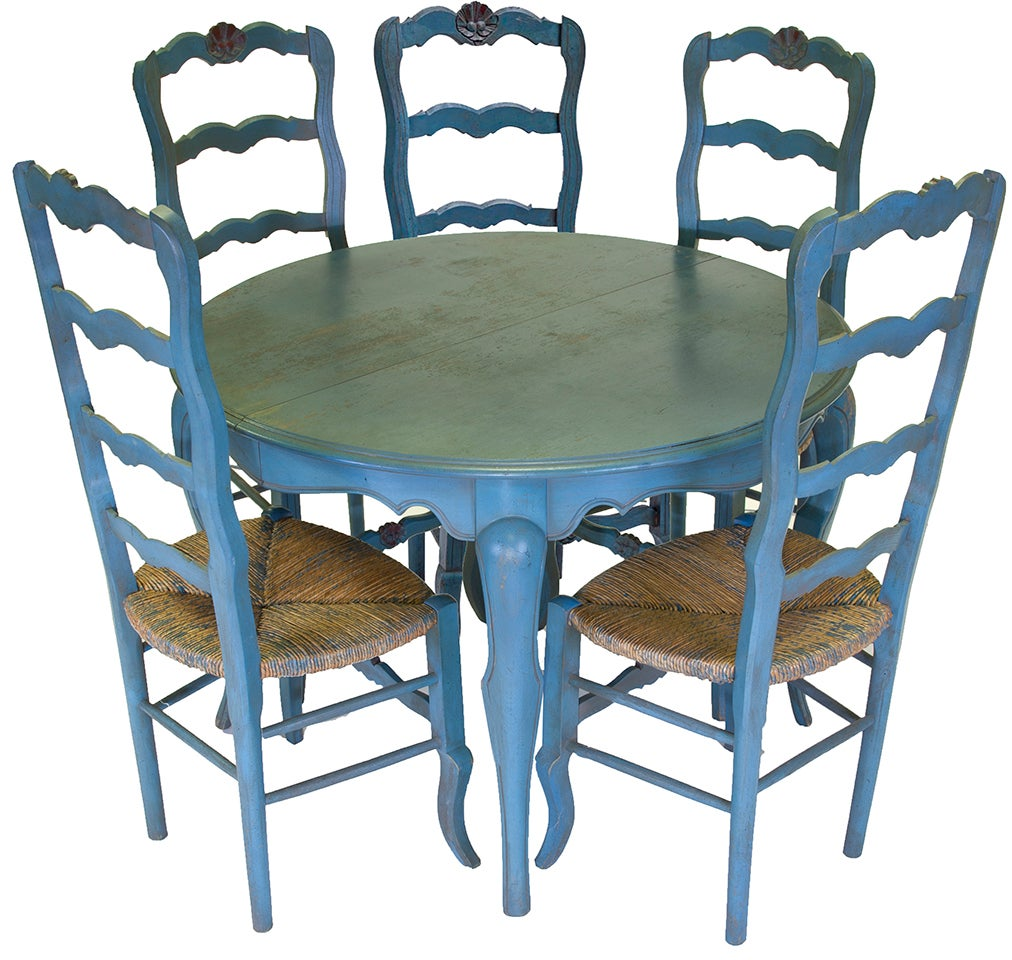 Beautiful grange French country provincial blue dining table and chairs includes hand-carved ladderback chairs with thin painted ruche, woven straw, seats and red toned sunflower motif at crowns. The table is a spring and coil operating design with