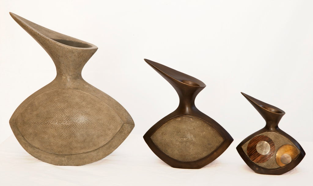 Large teak wood vase with bronze smaller vases is Mid-Century in period and design as well. Colors in shades of green and bronze tones with the two smaller vases being heavy bronze and the larger vase made of light wood.