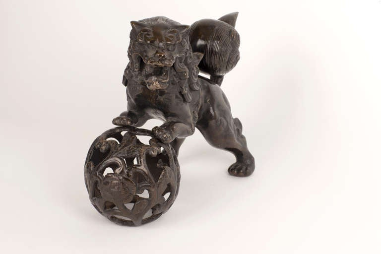 This cast iron piece features a statuary male Chinese guardian Lion (Foo Dog) proudly balancing both hands atop an embroidered ball, representing supremacy over the world. A traditionally and symbolically powerful representation of pre-modern China.