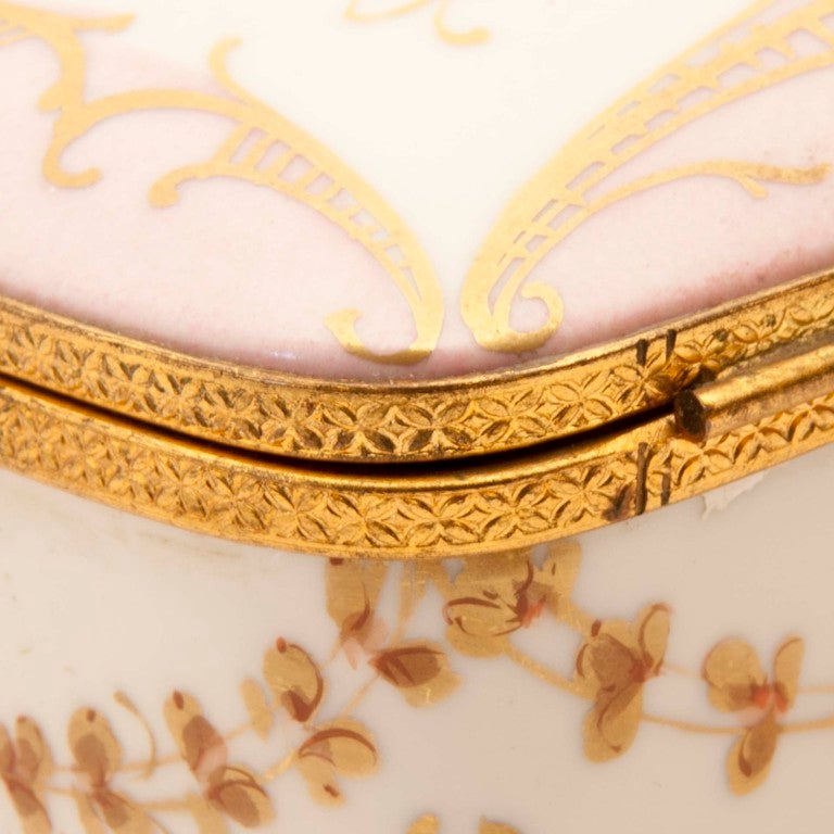 Beautiful porcelain Limoges box hand-painted rose flowerettes adorned with painted gold designs and gold hardware.