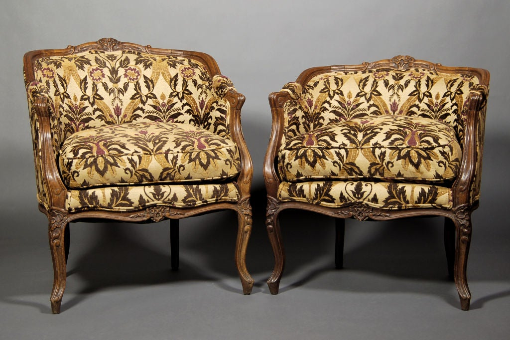 Beautiful Antique French Bergeres with carved floral wood patterns, and cabriole legs. Have been re-upholstered with tapestry fabric within the past half century. Original straw, nails and bottom stuffing still in tact.