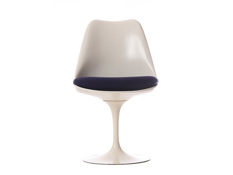 A dining chair with an upholstered seat and white enameled cast iron pedestal base.