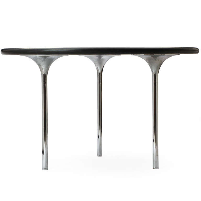 A Minimalist three-legged table having a round bull-nosed black granite top and grooved edge atop three through-connected solid polished chrome tapered support legs, designed by the architects Katavalos, Littel & Kelly for Laverne International.