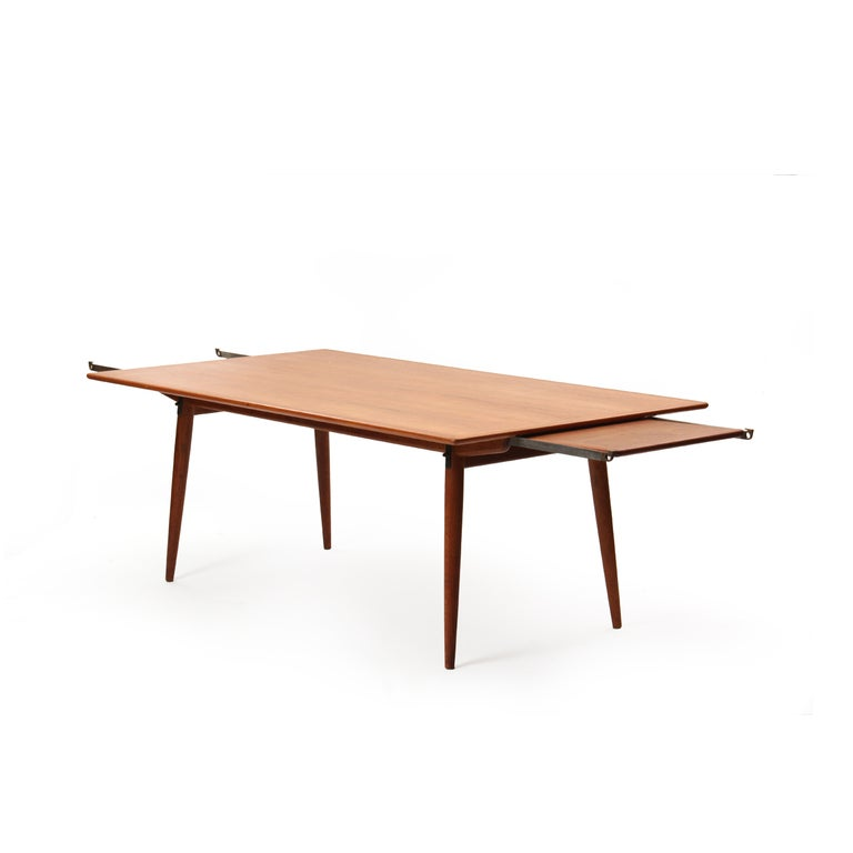 A rectangular dining table with a teak top concealing steel and brass pullouts and an innovative hidden leaf storage on a fumed oak base with splayed, tapered dowel legs. Two leaves are 17.5