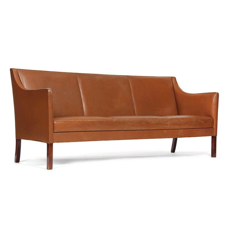 A sofa with a raised, tight back and sloping arms, retaining the original tan leather upholstery, on rosewood legs.