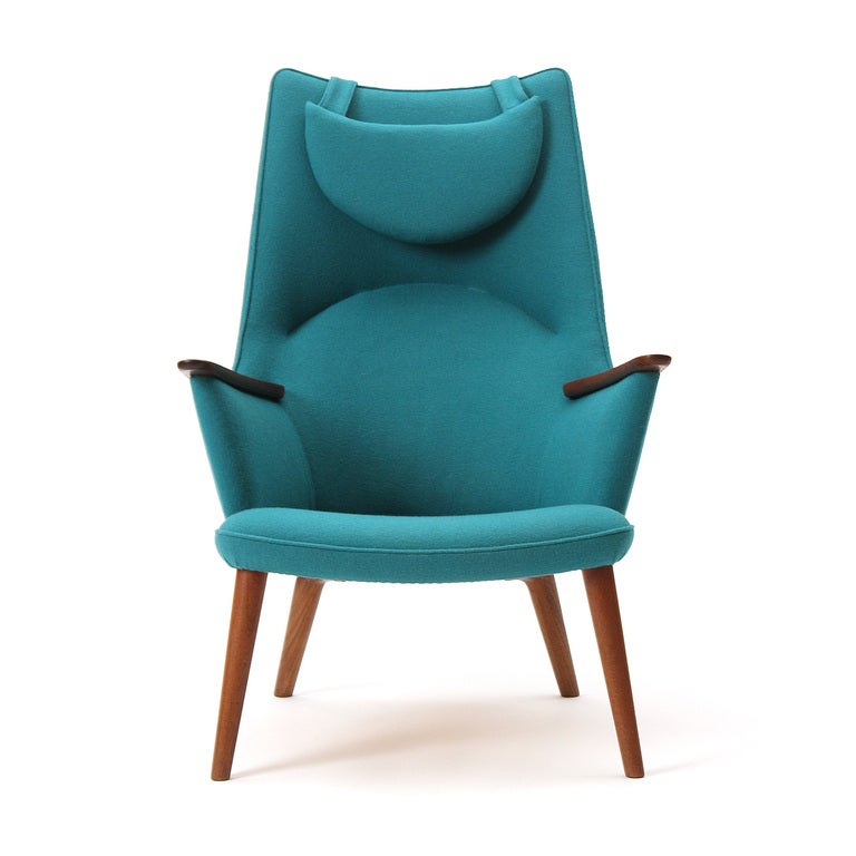 A high back lounge chair with teak arms and legs and new turquoise wool upholstery. 