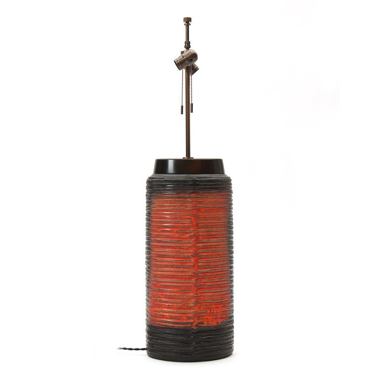 An oval ceramic table lamp with a black glaze and a raised, ribbed red design. Measure: Base height is 21.5