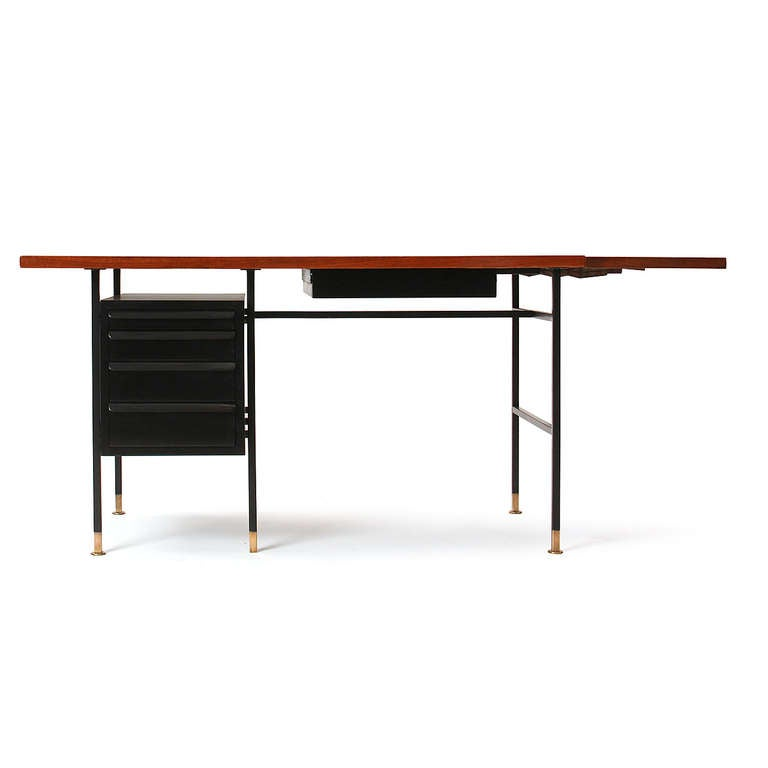 An architectural drop-leaf desk with a trapezoidal walnut top floating above a bank of drawers (with open shelving on the back) suspended within a painted metal frame and brass feet. Measures: 68