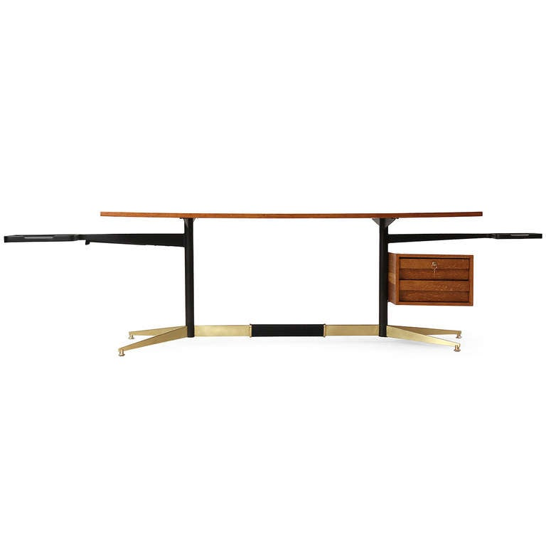 A rare and superb modernist desk having a spare architectural structure with pivoting cantilevered work surfaces and a floating top and keyed bank of drawers executed in a highly figured tiger oak.
