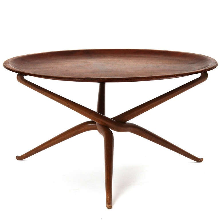 A finely crafted and elegant craft movement tray table with a removable top and sinuous hand carved intertwining legs.