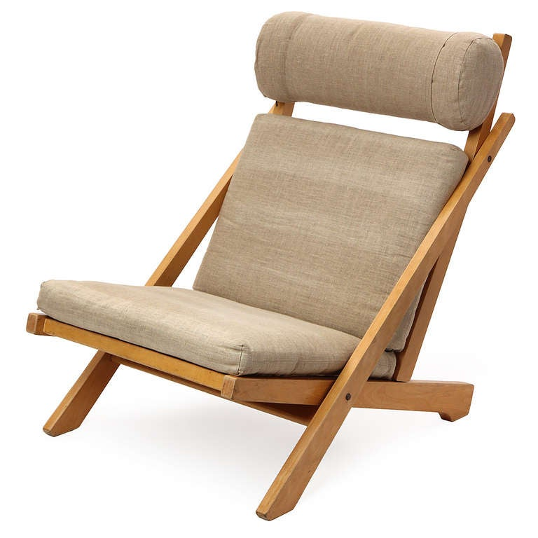 An architectural low lounge chair having an exposed beech slat-backed frame with flag halyard weaving and soft, light grey linen upholstery; the headrest is adjustable.