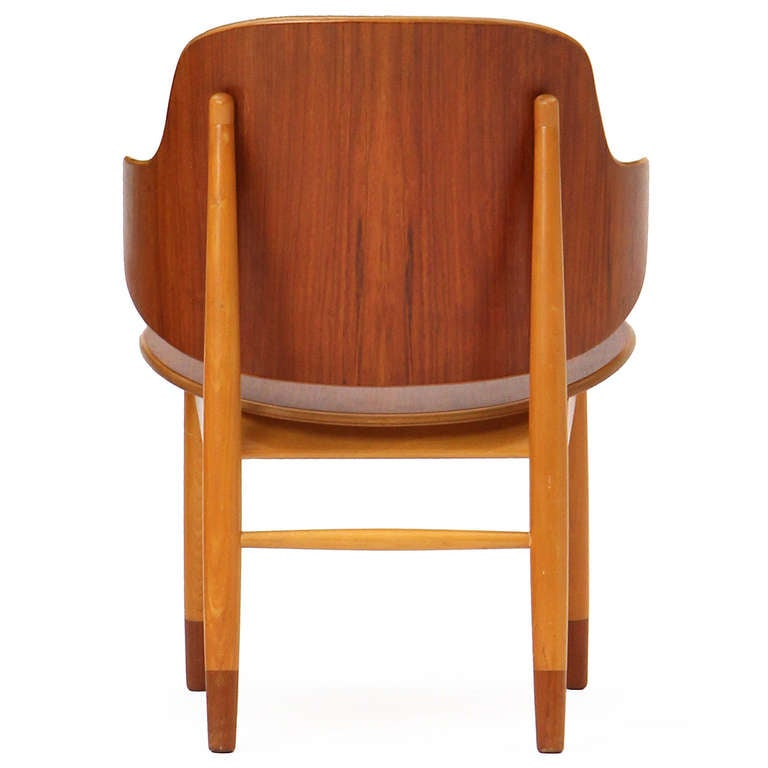 A sculptural lounge chair with a teak plywood seat and back on an expressive architectural exposed beech frame with teak tipped legs.