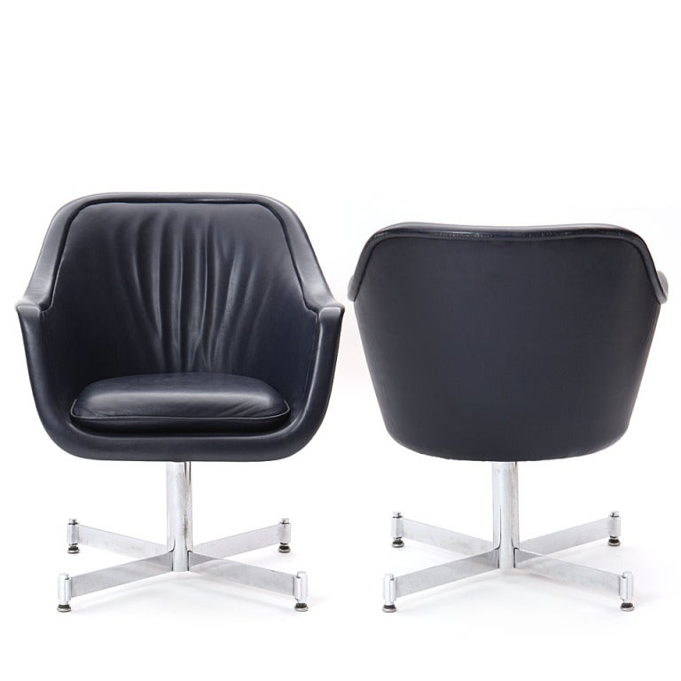A barrel-back desk chair with the original channel-stitched blue leather upholstery, on an X-form base. Casters can be added.