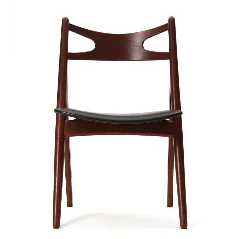 A teak 'Sawbuck' dining or desk chair with a black leather seat.