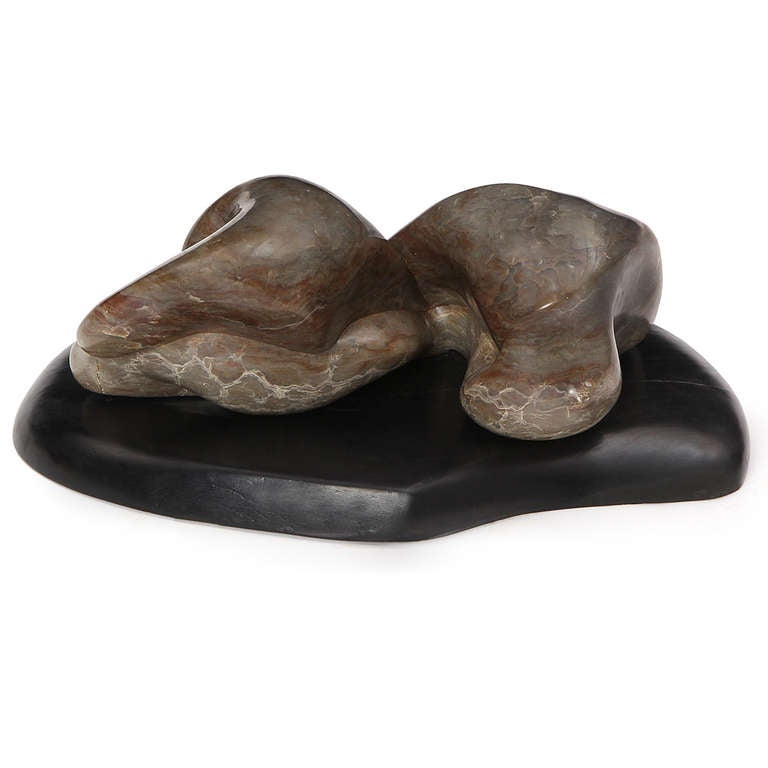 An abstract sculpture carved of richly figured marble and mounted on an organically shaped lacquered wooden base.