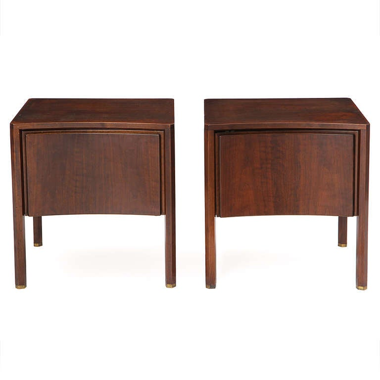A pair of bow-fronted night stands in dark walnut each having a single door and hexagonal legs with brass feet.