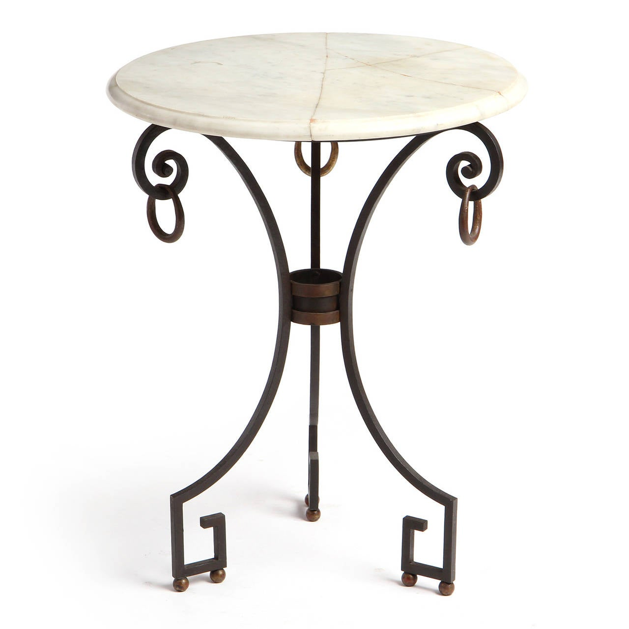 An occasional table having a wrought iron base with Greek Key feet and brass ball and ring embellishment supporting a round cream marble top with a beveled edge.