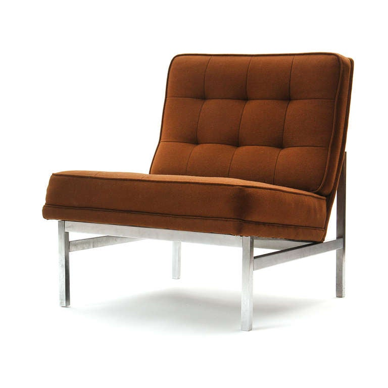 A lounge chair formed by an armless button-tufted upholstered seat resting on a matte steel, rectilinear architectural frame.