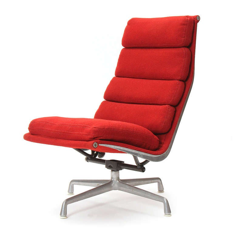 An armless soft pad swivelling lounge chair in original red wool channeled upholstery by Charles Eames for Herman Miller.
