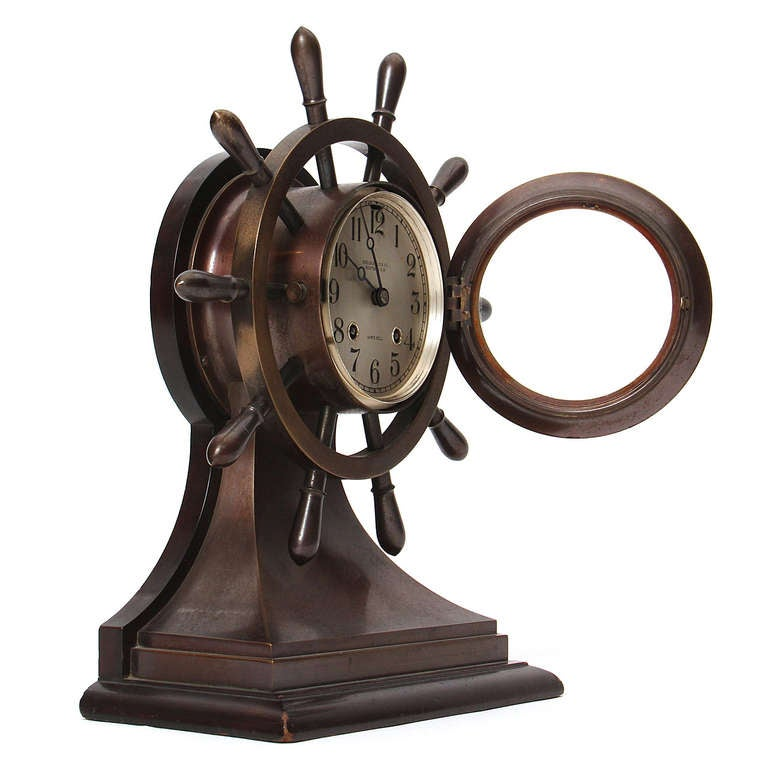 A finely crafted bronze clock in the form of yacht steering wheel made by Chelsea Clock Company, Boston, Massachusetts, having a hinged bezel, silvered dial with Arabic numerals, eight-day time and ship's bell striking lever escapement movement.
